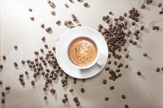 テーブルのヴィンテージの背景にコーヒー豆とコーヒーカプチーノのカップ