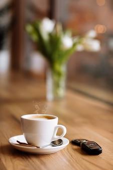 커피 한 잔, 자동차 원격 키, 커피숍의 나무 테이블에 있는 꽃병, 선별적인 초점. 프리랜서의 개념입니다. 복사 공간입니다.