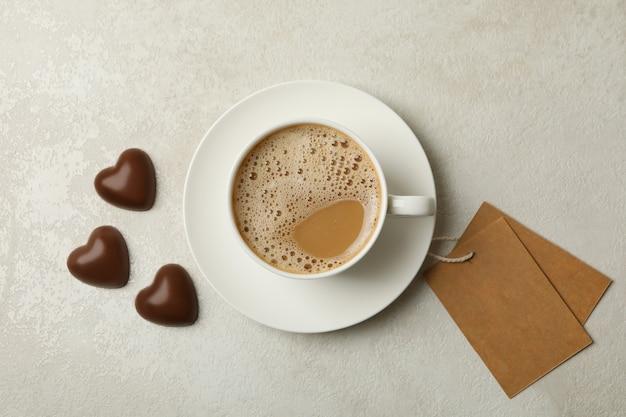 Чашка кофе, шоколадные сердца и пустые теги на белом текстурированном фоне