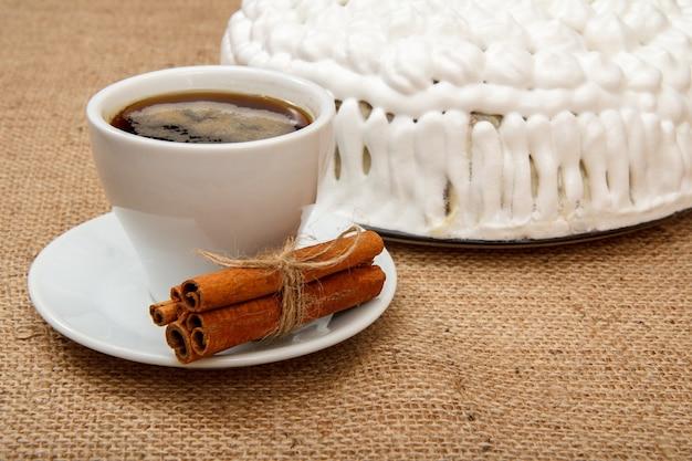 荒布を着たテーブルの上にホイップクリームで飾られた一杯のコーヒー、シナモン、ビスケットケーキ
