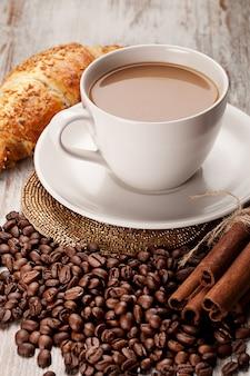 Чашка кофе, корица, круассан, на деревянном фоне