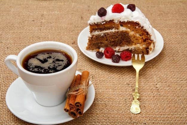 一杯のコーヒー、シナモン、フォーク、そして荒布を着たテーブルの上にホイップクリームとラズベリーで飾られたビスケットケーキのスライス