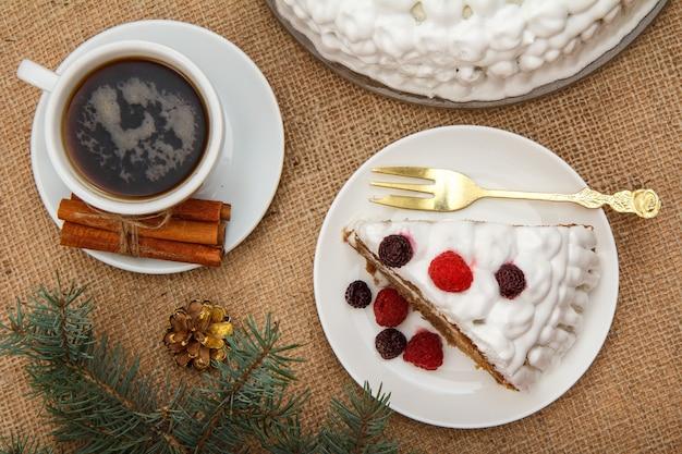 一杯のコーヒー、シナモン、フォークとビスケットケーキのスライス、荒布を着たテーブルの上のトウヒの枝。上面図。