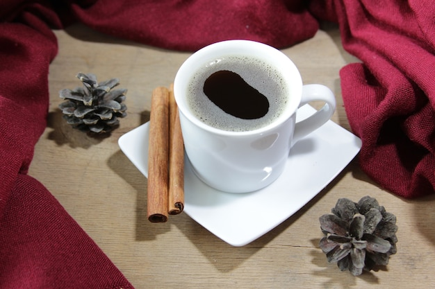 나무 배경에 커피 계피 스틱과 솔방울