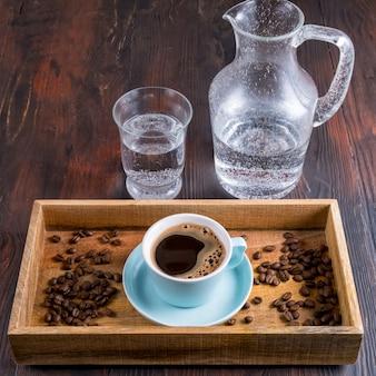 Чашка кофе, кофейные зерна и вода в деревянной коробке на темном деревянном