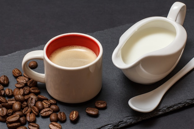 Чашка кофе, кофейные зерна, ложка и кувшин сливок на черном фоне. вид сверху.