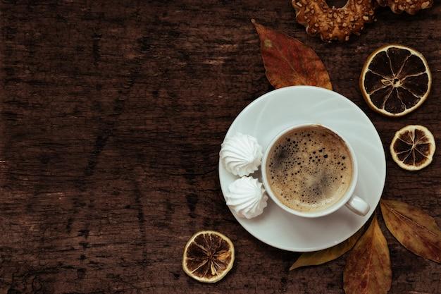 Чашка кофе, печенье и осенние листья на деревянном столе, вид сверху,