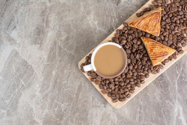 木の板にコーヒー、クッキー、コーヒー豆のカップ。高品質の写真
