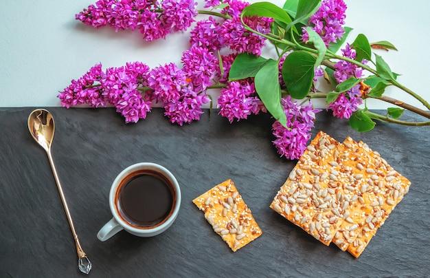 Чашка кофе, печенье с семечками и сиреневые цветы на столе. романтический завтрак.