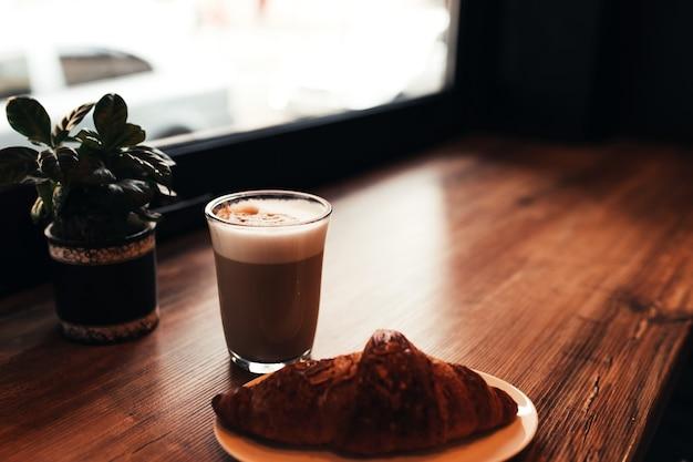 一杯のコーヒー、カフェの窓の近くのテーブルでクロワッサン