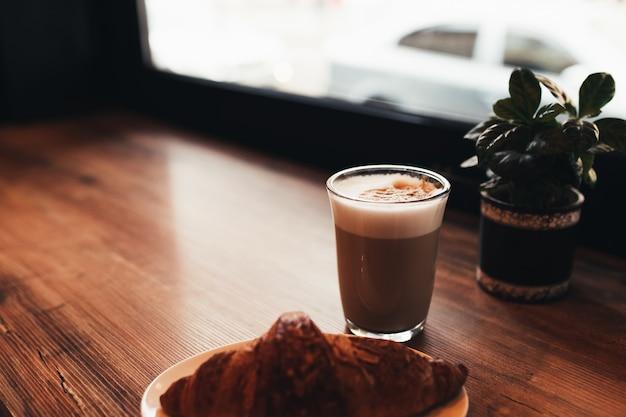 Чашка кофе, круассан за столом у окна в кафе Premium Фотографии
