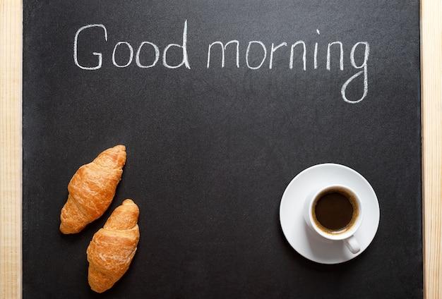 一杯のコーヒー、クロワッサン、黒板に「おはよう」と書かれています。伝統的な朝食、一日のコンセプトの良いスタート。メニュー用のスペースをコピーします。