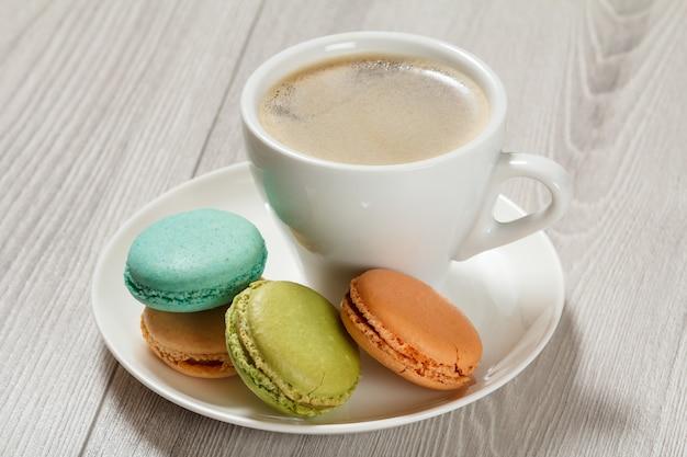 白い磁器の皿に異なる色のコーヒーのおいしいマカロンケーキのカップ