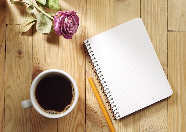 Чашка кофе, сушеные розы и блокнот на деревянном столе