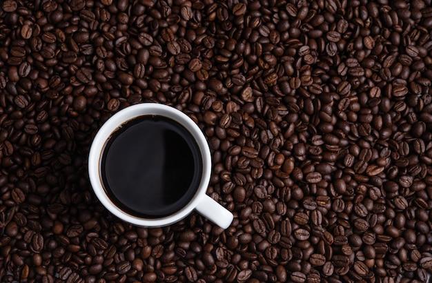 一杯のコーヒーエスプレッソコーヒー豆ブラウンシードテクスチャ背景の完全な壁紙