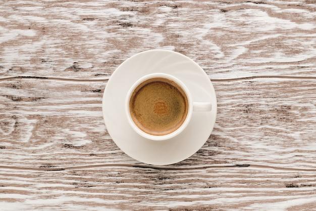 木製のテーブル、上面図にコーヒーエスプレッソのカップ