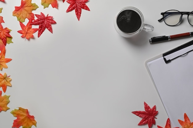 Чашка кофе, очки, буфер обмена и кленовые листья на белом фоне.