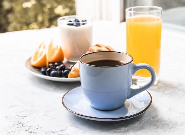 Чашка кофе на завтрак с соком, апельсином, черникой и йогуртом на бетоне