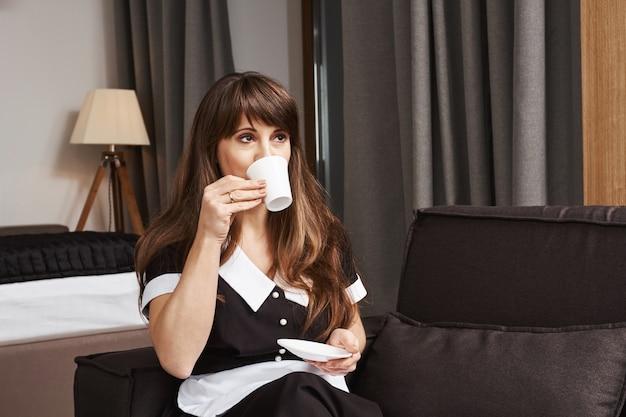 Чашка кофе для домработницы года. портрет мечтательной аккуратной горничной в форме, потягивая чай, глядя в сторону и сидя на диване, смотря телевизор, перерыв в уборке квартиры