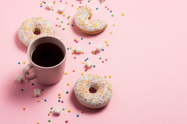 Чашка кофе, свежие вкусные сладкие пончики на розовом фоне. концепция фаст-фуд, пекарня, завтрак, сладости. минимализм. плоская планировка, вид сверху, копия пространства.