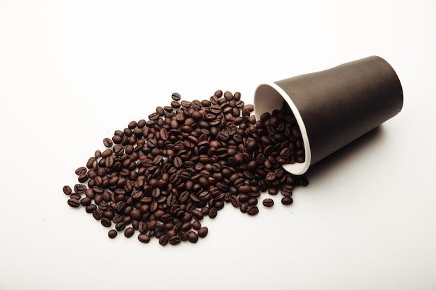 Чашка кофе, полная кофейных зерен на белом фоне