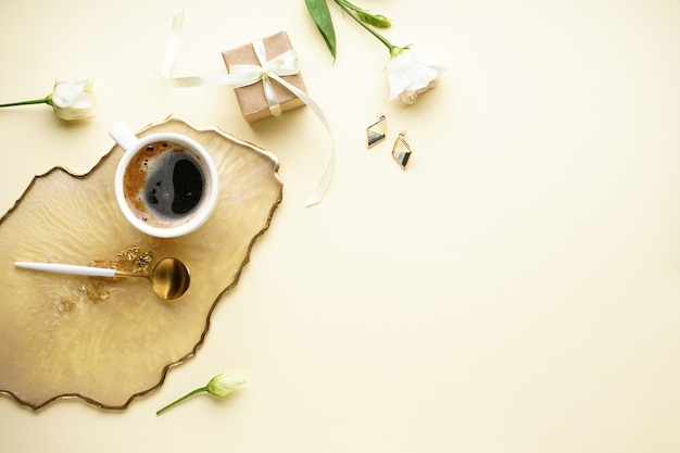 Чашка кофе, подарочная коробка и красивый цветок