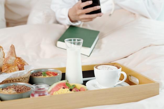 ベッドで休んでいる女性の前の木製トレイにコーヒー、非乳製品ヨーグルト、果物、パン、グラノーラボウルのグラス
