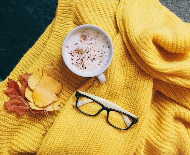 Чашка кофе, бокалы и ярко-желтый свитер