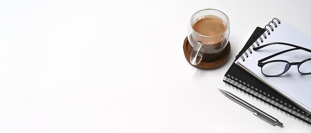 白いテーブルの上のコーヒー、グラス、ノートブックのカップ。スペースをコピーします。