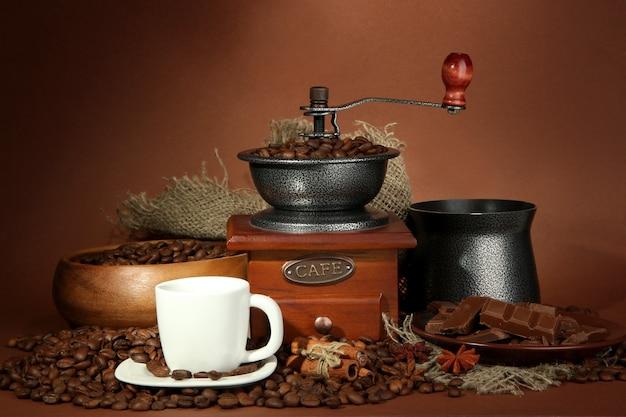 Чашка кофе, кофемолка, турок и кофейные зерна на коричневом фоне