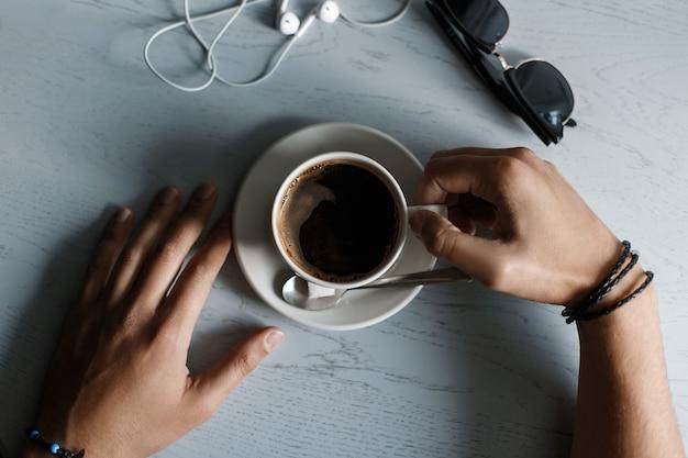 木製のテーブルの上に横たわっているコーヒー、ヘッドフォン、サングラスのカップ