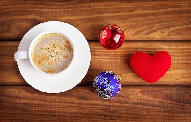 나무 배경에 커피, 심장, 크리스마스 거품 한 잔.
