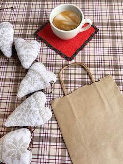 테이블에 커피, 하트, 쇼핑백의 컵