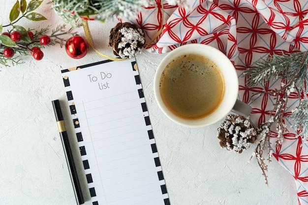 Чашка кофе праздничные украшения и список дел на белом столе, планирование рождества