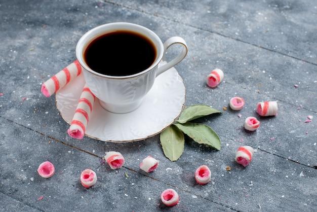 灰色のコーヒーキャンディーの甘い飲み物にピンクのスティックキャンディーと一緒に熱くて強いコーヒーのカップ