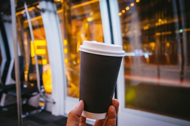 空港で一杯のコーヒーマンの手と黒いカップ