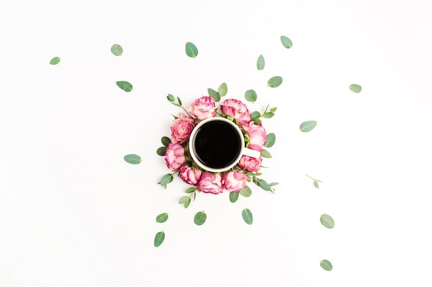 ピンクのバラの花のつぼみとユーカリの枝のフレームに入れた一杯のコーヒー。フラットレイ、トップビュー