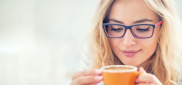 幸せな若い女性の手にコーヒーのカップ。