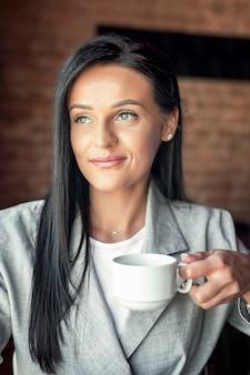 女性の手でコーヒーカップ