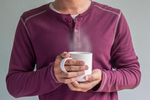 男の手でコーヒーのカップ