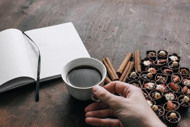 Чашка кофе в мужской руке с шоколадными конфетами и блокнотом