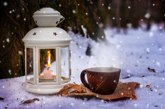 夕方に古い木の近くにキャンドルとランタンの横にある冬の森で一杯のコーヒー_