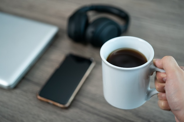 スマートフォン、木製のテーブルの上のラップトップと職場のオフィスの机でコーヒーのカップ。