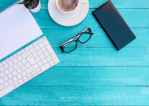 청록색 나무 책상에 커피, 키보드, 노트북, 식물, 안경 및 흰색 빈 시트 컵