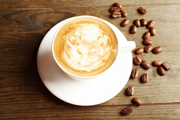 나무 표면에 곡물과 커피 라떼 아트 컵