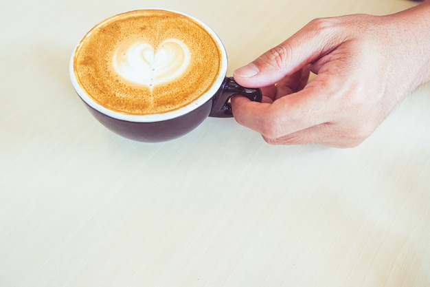 朝日光の下で古い木製の背景に緑の詩のマグカップでコーヒーラテのカップ