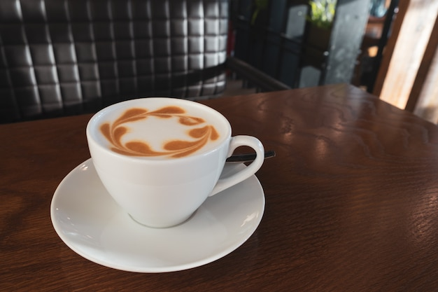 Latte чашки кофе на деревянном столе в кафе.