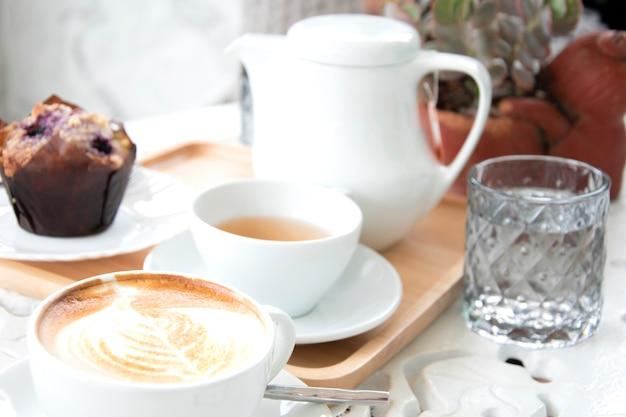 お茶とマフィンとコーヒーラテのカップ。モーニングコーヒーホワイトトーン。