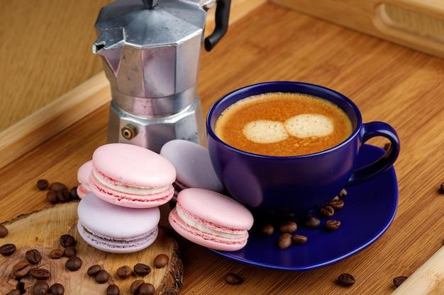 大皿にコーヒーマカロンとコーヒー豆のカップと木製トレイに間欠泉コーヒーメーカー