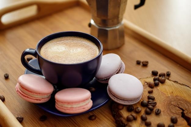 木製トレイの大皿にコーヒーマカロンとコーヒー豆のカップ